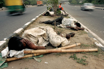 Homeless Indians sleep on a pavement of New Delhi