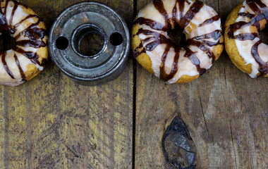 Retro donut cutter with donuts close up on rustic wood table