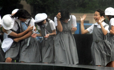 JAPANESE SCHOOLGIRLS PLAY BY WATER FOUNTAIN IN TOKYO.