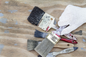 Man's hand wearing white glove holding old grunge paintbrushes on dirty grunge vintage wooden background