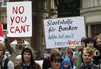 Protesters hold up banners as German Chancellor Merkel gives a speech during a rallay of the CDU in Goerlitz