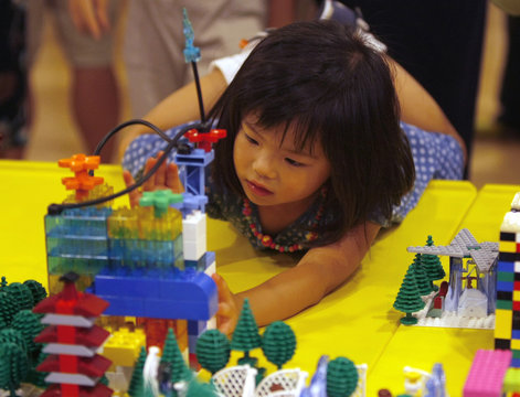 A girl gives a last touch to her Lego work on Dream City which was built by about 100,000 pieces of Lego blocks in Tokyo