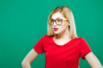 Closeup Portrait of Surprised Girl Wearing Short Red Top and Eyeglasses. Sensual Pretty Blonde with Long Hair is Posing on Green Background in Studio.