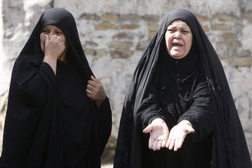 Women react after bomb attacks at parking lot in Baghdad