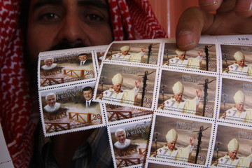 Jordanian man displays sheets of stamps, showing images of Pope Benedict XVI and Jordan's King Abdullah, he bought at a post office branch in Amman