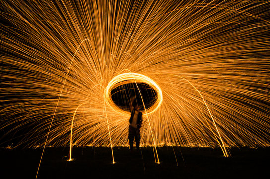 Abstract background from spinning steel wool on cliff at night time