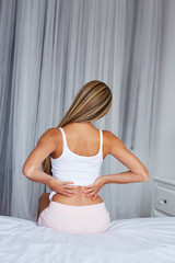 Young woman sitting on a bed with back pain