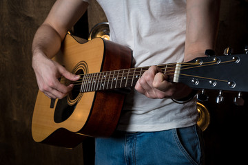 Playing guitar. Acoustic guitar in the hands of the guitarist. Horizontal frame
