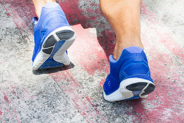 Man wearing sport shoes warming up on old grunge gym floor, sport exercise concept