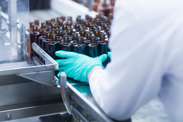 Workers arranging bottles on conveyor belt on production line in pharmaceutical plant, mid section
