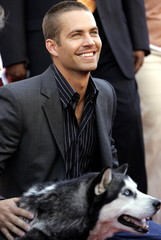 Cast member Paul Walker smiles as he pets one of his co-stars Siberian husky DJ at the world premier..