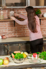 A woman in the kitchen puts something on the shelf in the defocus, and on the table lie fresh vegetables