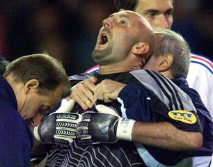 France's goalkeeper Fabien Barthez (C) receives assistance as he gasps for breath after goal mouth c..