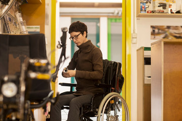 Woman in wheelchair in bicycle repair shop