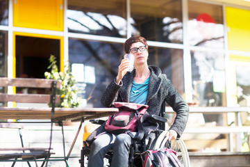 Woman in wheelchair, sitting outside cafe, drinking cold drink