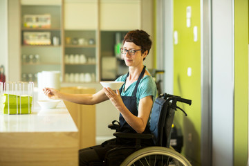 Woman in wheelchair, working in restaurant, holding bowl of food