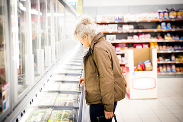 Mature woman in supermarket, looking in freezer cabinet