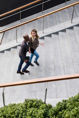 Young businessman and woman moving up city stairway talking