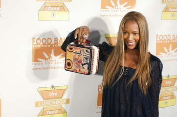 Model Campbell holds up lunch box she designed for charity auction to benefit hunger relief organizations in New York