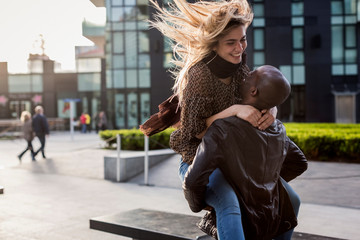 Romantic young man lifting girlfriend in city