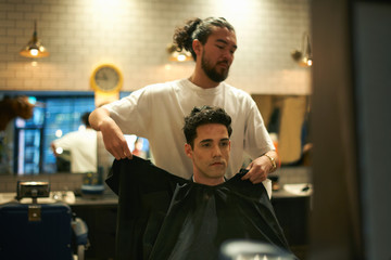Barber putting gown onto male customer in barber shop