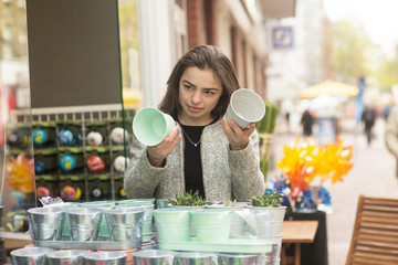 Young woman comparing flower pots on market stall
