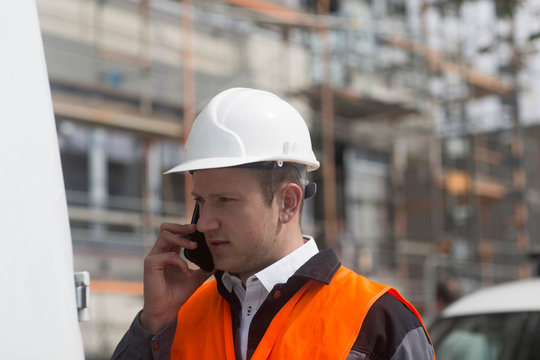 Young male civil engineer making smartphone call on construction site