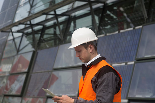 Young male engineer looking at digital tablet at solar panel site