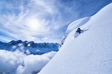 Woman skiing down steep mountainside in Swiss Alps, Gstaad, Switzerland