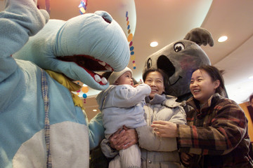 A CHINESE FAMILY ENJOYS A LIGHT MOMENT WITH WORKERS DRESSED AS WESTERN CARTOON CHARACTERS AT A ...