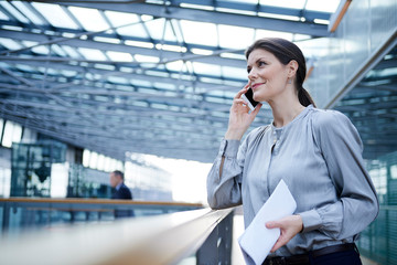 Businesswoman making smartphone call on office balcony