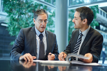 Two businessmen meeting over paperwork at office desk