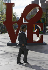 """A man walks past an art piece spelling the word """"Love"""" beside the Taipei 101 building in the business district of Xinyi in Taipei"""