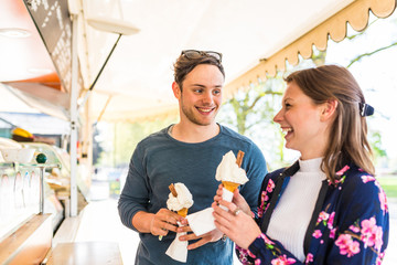 Young couple buying ice cream cones at ice cream parlour in Battersea Park