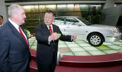 Georgia state Governor Perdue and chairman of Kia Motors Chung look around Kia Motors showroom in Seoul