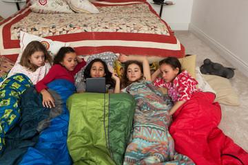 Girls in sleeping bags at slumber party using digital tablet