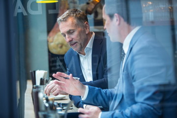 Two businessmen having discussion in restaurant window seat