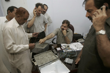 Security officials examine explosive material they recovered from an abandoned car in Karachi