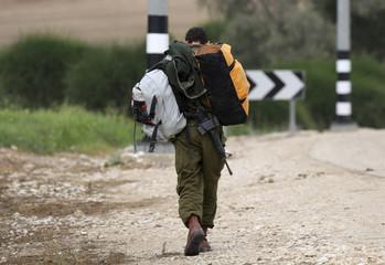 Israeli soldier carries bags to bus stop at Beeri