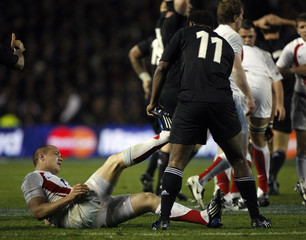 New Zealand All Blacks' Sivivatu helps England's Brown with cramp during their international rugby test match at Eden Park in Auckland