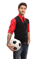 Tattooed guy holding a football and looking at the camera
