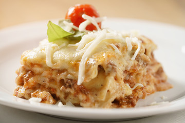 homemade lasagna portion on white plate on wood table, shallow focus