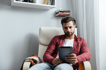 Concentrated young bearded man using tablet computer