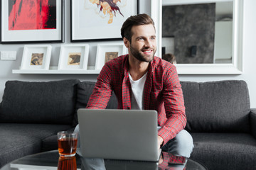 Happy young bearded man using laptop computer.