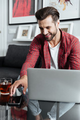 Happy young bearded man using laptop computer holding telephone
