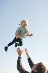 Father tossing daughter into air