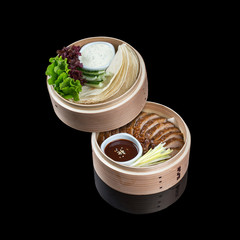 Duck in Beijing in a bamboo dish, with a flat cake, sauce and cucumber. On a black background with reflection