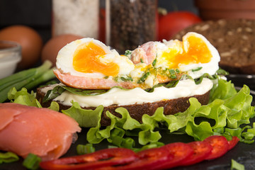 Toast with salmon, pepper, cream cheese, chives and poached egg