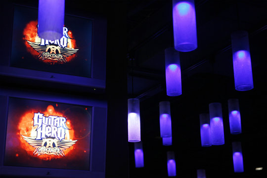 "Television screens display the logo for the new video game ""Guitar Hero: Aerosmith"" before a press conference in New York"