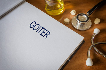Goiter written on book with tablets. Medicine concept.